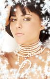 Pearl desire with snowflakes. Portrait of mysterious brunette with white pearls and snowflakes Royalty Free Stock Photography