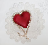 Pearl Draped Heart on Doily Stock Photos