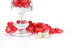 Pearl ear studs and red pomegranate seeds Stock Images