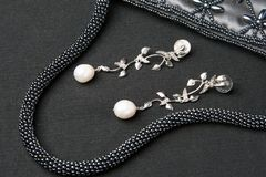 Pearl earing jewlery. Party accessories such as small bag and earings over dark background stock images