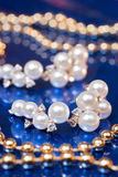 Pearl earring and golden beads Stock Image
