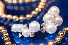 Pearl earring and golden beads Royalty Free Stock Photography
