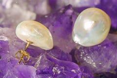 Pearl earrings on ametyst background. Pair of pearl earrings on ametyst background Stock Photos