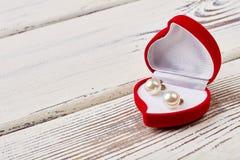 Pearl earrings in heart-shaped box. Stock Photo