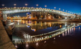 Pearl embrace of Patriarchal bridge. The curved arch of Patriarchal bridge with reflection in winter river in the early morning and the Moscow Kremlin at the Stock Photography