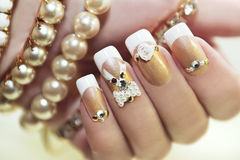 Pearl French manicure. Pearl French manicure with rhinestones and embellishments Stock Photos