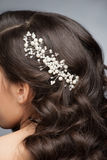 Pearl hair accessory. Closeup of brown hair with stylish pearl hair accessory, rear view Royalty Free Stock Photo