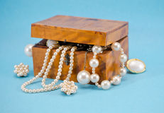 Pearl jewelry defocus in retro wooden box on blue Stock Photo