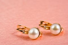 Pearl jewelry on rosy folds stock image