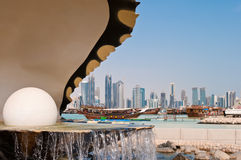 The pearl landmark on the Doha corniche. The pearl inside a giant clam, a famous landmark on the corniche in Doha, Qatar.  The city skyline is visible in the Stock Images