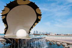The pearl landmark on the Doha corniche. The pearl inside a giant clam, a famous landmark on the corniche in Doha, Qatar.  The city skyline is visible in the Royalty Free Stock Image