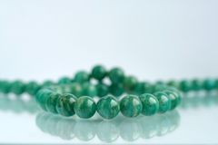 Pearl necklace. Green pearl necklace reflecting on studio background Royalty Free Stock Image