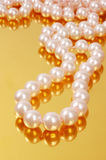 Pearl necklace. Pink pearl necklace on gold background Stock Photos