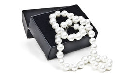 Pearl necklace. Black gift box and white pearl necklace over white Royalty Free Stock Photography