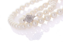 Pearl necklace. With silver flower with reflection on white background stock images