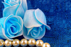 Pearl necklace with blue satin background Royalty Free Stock Photos