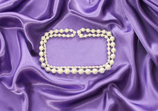 Pearl necklace on blue silk drape Royalty Free Stock Photos