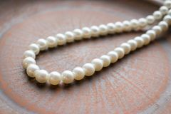 Pearl necklace on a brown clay plate. Close up of thread of whit Stock Images