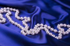 Pearl necklace on dark blue satin fabric stock images