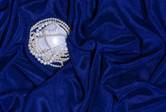 Pearl necklace on draped fabric Stock Images
