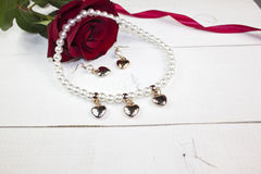 Pearl necklace with earring with golden hearts on white wood. Pearl necklace with earring with golden hearts, red rose, red ribbon on white wood royalty free stock photos