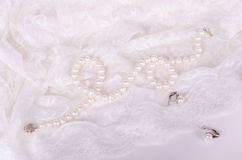 Pearl necklace and earrings on white lace cloth Royalty Free Stock Photo