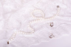 Pearl necklace and earrings on white lace cloth Stock Photo