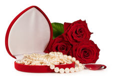 Pearl necklace in a gift box with a bouquet of red roses Stock Images