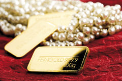 Pearl necklace and gold bars Royalty Free Stock Images