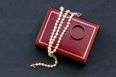 Pearl necklace, and gold ring. Royalty Free Stock Photo