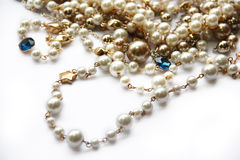 Pearl necklace. Pearl necklace and golden decoration  on white background Stock Images