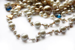 Pearl necklace. Pearl necklace and golden decoration  on white background Royalty Free Stock Photos