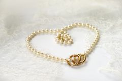 Pearl necklace heart with golden rings. Heart of pearl necklace with two golden rings resting on white wedding lace Stock Image
