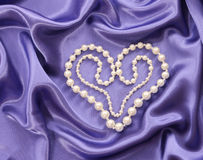 Pearl necklace in heart shape on blue silk fabric Royalty Free Stock Images