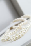 Pearl necklace, in its box. A composition with a pearl necklace and its box, detail, portrait cut Stock Images