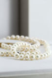 Pearl necklace, in its box. A composition with a pearl necklace and its box, detail, portrait cut Royalty Free Stock Photo
