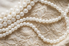 Pearl necklace on lace clothes Stock Images