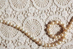 Pearl necklace on lace fabric. Pearl necklace on ivory-colored lace cloth royalty free stock photo