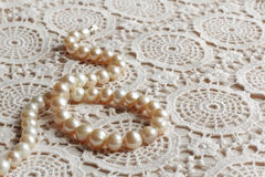 Pearl necklace on lace fabric Royalty Free Stock Photography