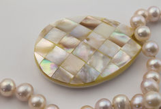 Pearl necklace with mother of pearl inlay pendant  on wh Stock Image