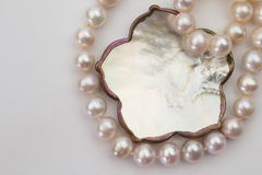 Pearl necklace and mother of pearl pendant isolated on white. Top lay pale pink pearl necklace and mother of pearl pendant isolated on white Stock Photo
