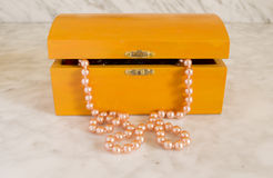 Pearl necklace in an old orange coffer Royalty Free Stock Photography