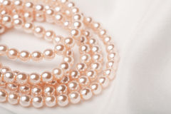 Pearl necklace over white silk Royalty Free Stock Photos