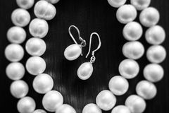 Pearl necklace and pearl earrings on a black background.  stock photography