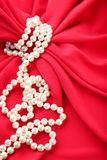 Pearl necklace. On red satin fabric royalty free stock photography