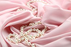 Pearl necklace. On pink satin fabric stock image