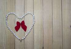 Pearl necklace with red bow in a heart Royalty Free Stock Photos
