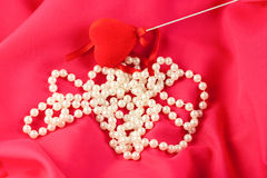 Pearl necklace with red heart on red silk Royalty Free Stock Photo