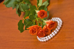 Pearl necklace and red roses Royalty Free Stock Photos