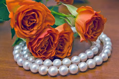 Pearl necklace and red roses Royalty Free Stock Photography
